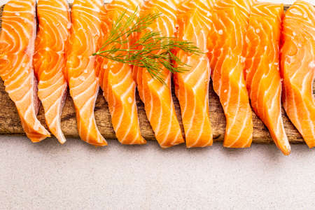 Slices of fresh salmon fish. Raw ingredient for cooking healthy seafood. Concept omega 3 containing food. Vintage wooden cutting board, stone concrete background, copy space, top view
