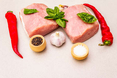 Raw pork meat loin with fresh vegetables and dry spice. Animal protein healthy cooking concept. Chili and black pepper, garlic, basil, sea salt. Light stone concrete background, copy space