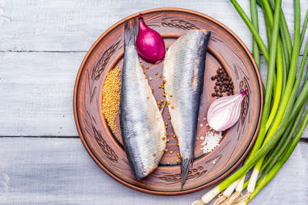 Traditional Norwegian slightly salted herring. Healthy seafood concept. Vegetarian ingredient with fresh onion, dry spice on ceramic plate. Rustic style, wooden boards background, copy space, top view