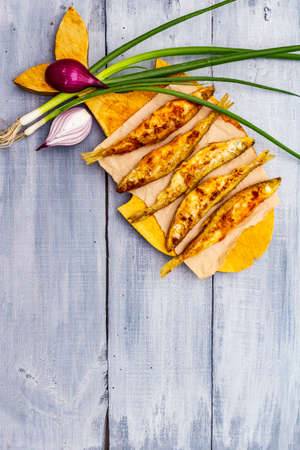 Fried smelt with fresh onions. Healthy seafood with the smell of cucumber, crispy breading. On a wooden board in the shape of a fish. Gray wooden boards background, copy space, top view