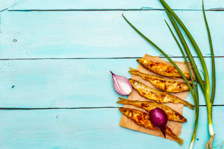 Fried smelt with fresh onions. Healthy seafood with the smell of cucumber, crispy breading. On a parchment, turquoise wooden boards background, copy space, top view