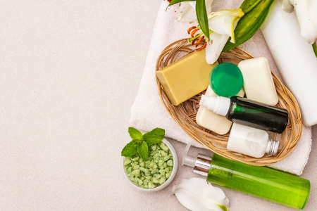 Healthy and beauty spa flower concept. Natural ingredients for relaxation. Mint salt, olive soap, green tea essential oil, towels, shower gel. Stone concrete background, copy space, top view