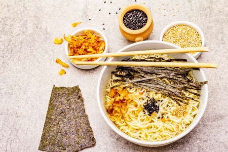 Noodles with seaweed, tuna flakes and sesame seeds. Healthy vegan (vegetarian) eating. In ceramic bowls, stone concrete background, copy space, top view, close up