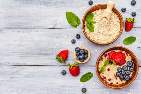 Healthy breakfast vegetarian (vegan) concept. Oatmeal with fresh berries and mint. Ethnic ceramic bowls, rustic style. Wooden boards background, copy space, top view