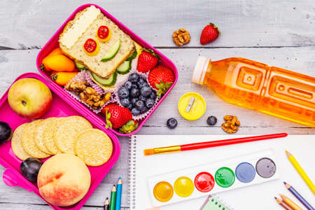 School lunch box with sandwich, fresh fruits, vegetables, cookies, juice and nuts. Healthy eating habits for kids. Back to school concept. With school supplies, wooden boards background, top view