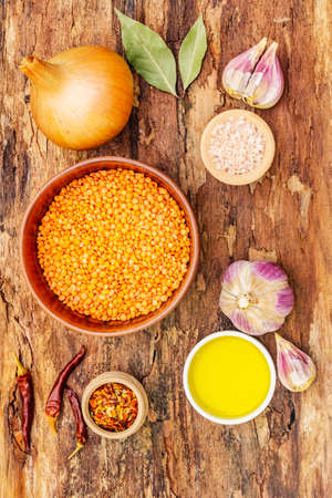 Ingredienti grezzi per il piatto tarka dal, Daal Curry, zuppa di curry piccante tradizionale indiana Dhal. Lenticchia rossa secca, aglio, peperoncino, cipolla, olio. Sullo sfondo di corteccia di legno, vista dall'alto Archivio Fotografico