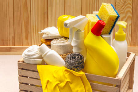 House cleaning product in wooden box. Spray, bottle, gloves, dishwashing sponge, scraper, gel air freshener. Stone concrete background, close up