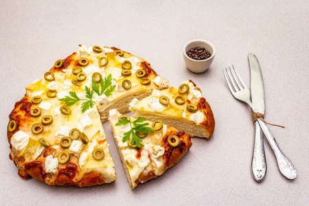 Italian focaccia with three types of cheese, green olives, black pepper and parsley. Traditional food concept, cut pieces with cutlery, on stone background