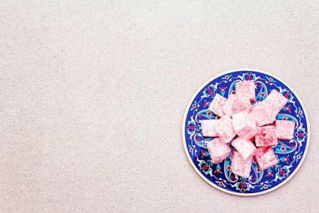Bonbons orientaux. Délice turc traditionnel Rahat lukum avec une rose sur céramique aux motifs folkloriques typiques. Fond de pierre, espace de copie, vue de dessus