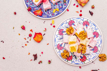Eastern sweets. Traditional Turkish delight Rahat lukum with a rose and citrus on ceramics with typical folk patterns. Stone background, close up, copy space, top view Stock Photo