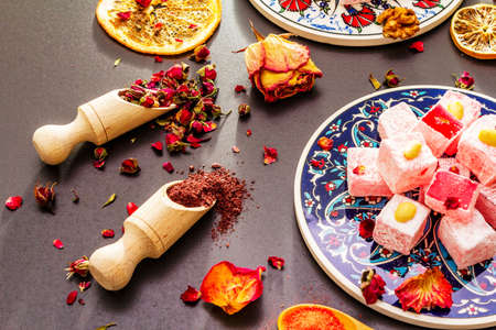 Eastern sweets. Traditional Turkish delight Rahat lukum with rose and citrus on ceramics with typical folk patterns. Fruit sugar, sumac in wooden shovels. Sun rays stone background close up