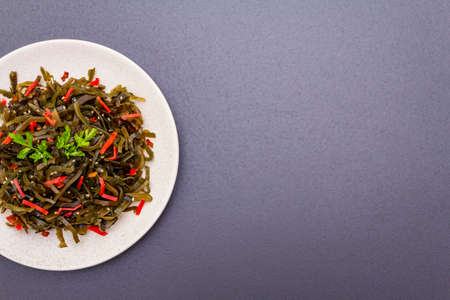Laminaria salad (Kelp) with red ginger and sesame seeds. Seafood rich in iodine and minerals. Healthy eating concept. Cooking food stone background, copy space, top view