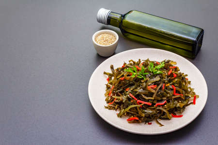 Laminaria salad (Kelp) with red ginger and sesame seeds. Seafood rich in iodine and minerals. Healthy eating concept. Cooking food stone background, copy space