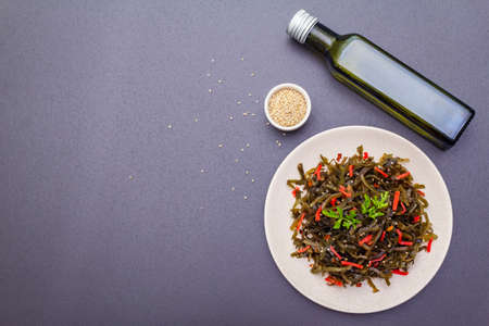 Laminaria salad (Kelp) with red ginger and sesame seeds. Seafood rich in iodine and minerals. Healthy eating concept. Cooking food stone background, top view, copy space