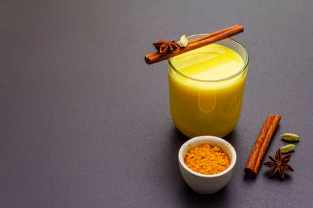 Golden turmeric milk. Cinnamon, cardamon, anise spices. Trendy healthy drink concept. In glass on stone background, copy space Stock Photo