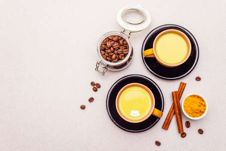 Golden turmeric cinnamon coffee latte. Trendy healthy hot drink concept. In ceramic cups on stone background, copy space, top view