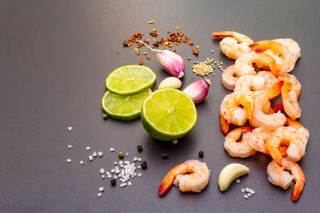 Fresh raw organic shrimps (prawns), spices, lime. Healthy vegetarian food concept. Black stone cooking background, close up