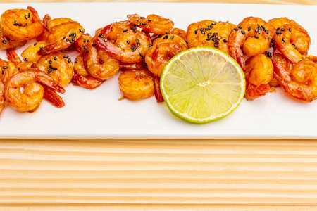 Fresh organic fried shrimp (prawns). Delicious seafood in teriyaki sauce with lime. On wooden boards background, close up.