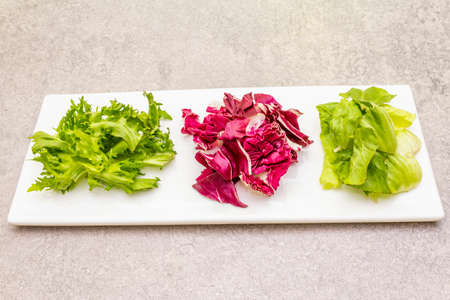 Vegan (vegetarian) healthy food concept. Fresh organic salad mix of radicchio, escarole endive and frize lettuce. On white ceramic plate on stone cooking background, close up Archivio Fotografico