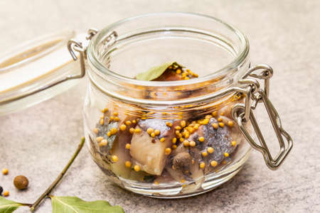 Slices of herring with spices in a glass jar. Mustard seeds, bay leaf, pepper mix. Healthy traditional food concept. Stone background, close up, macro Stockfoto