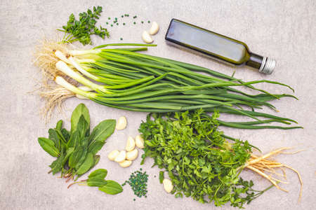 A bunch of fresh green onions, sorrel, parsley, garlic, olive oil and green pepper peas. Healthy vegetarian (vegan) food concept, ingredients for cooking. On a stone background, close up, top view 版權商用圖片
