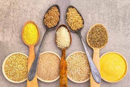 Healthy food vegetarian (vegan) concept. Assorted various organic cereals, legumes, whole grains. In ceramic bowls and wooden spoons on a stone background, top view