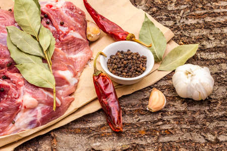 Raw pork shoulder with spices. Bay leaf, garlic, chili. On a wooden bark background, close up