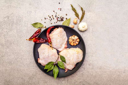 Raw chicken thighs with spices. Ingredients for cooking meat on a stone background. Hot and black pepper, garlic, rosemary, bay leaf, top view Stock Photo