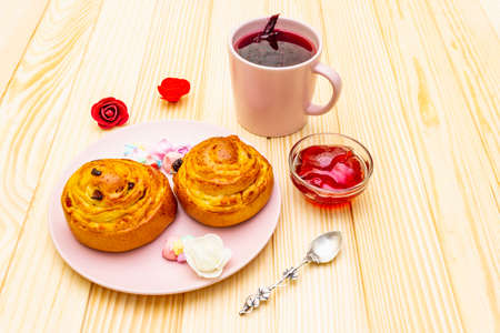 Karkade tea from hibiscus petals (Sudanese rose). Gentle romantic breakfast concept. Buns, meringues, strawberry jelly. On a wooden background