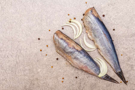 """Traditional Norwegian herring """"Matias Queen"""", whole carcasses. Ingredient for smorrebrod, snacks, antipasti. With sliced onion, black pepper, coriander. On stone background, top view, copy space"""