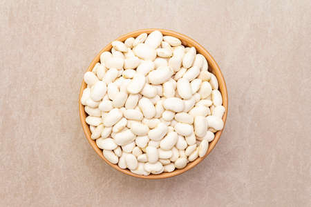 Dry lima beans in ceramic bowl on stone background, top view, wallpaper, close up