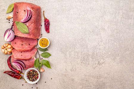Filetto di maiale crudo con verdure e spezie. Cucinare lo sfondo di carne, bistecca disossata di petto fresco su sfondo di pietra, spazio copia vista dall'alto Archivio Fotografico