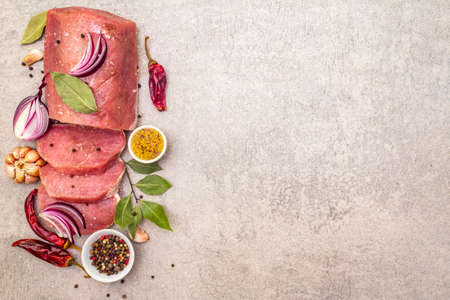 Raw pork tenderloin with vegetables and spices. Cooking meat background, fresh brisket boneless steak on stone background, top view copy space Stock Photo