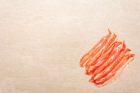 Smoked bacon slices. Raw stripes on stone background, top view