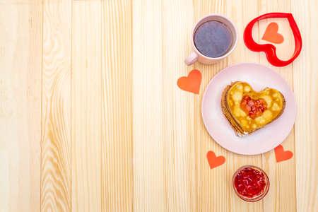 Tortitas en forma de corazón para un desayuno romántico con mermelada de fresa y té negro. Concepto de carnaval (carnaval). Sobre fondo de madera, vista superior. Foto de archivo