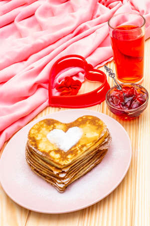 Heart shaped pancakes for romantic breakfast with strawberry jam and juice.