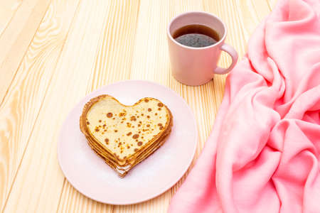 Heart shaped pancakes for romantic breakfast with strawberry jam and black tea. Shrovetide (carnival) concept. On wooden background.