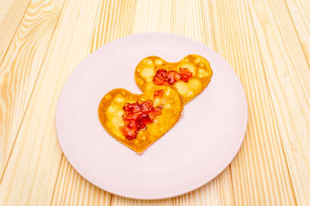 Heart shaped pancakes for romantic breakfast with strawberry jam. Stock Photo