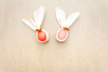 Easter bunny (rabbit) egg concept, table arrangement decoration. Pink (rosy) eggs with vintage cloth linen napkin (canvas) on stone background, top view.