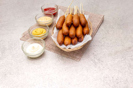 Corn dogs homemade with popular sauces. Traditional American street food. On stone background.