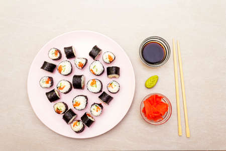 Romantic heart sushi dinner. Maki rolls with ginger, wasabi and soy sauce on rosy plate. Concept for Valentine's Day or March 8th. Stone background, top view.