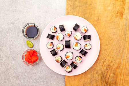 Romantic heart sushi dinner. Maki rolls with ginger, wasabi and soy sauce on rosy plate. Concept for Valentine's Day or March 8th. Stone and wooden background, top view.