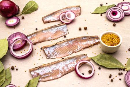 Filet de hareng salé norvégien mariné aux épices et oignons. Poisson mariné sur fond de pierre.