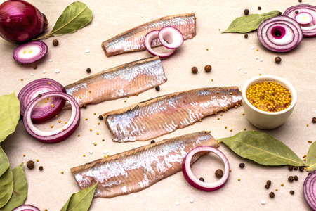 Fillet of pickled Norwegian salted herring with spices and onions. Marinated fish on a stone background.