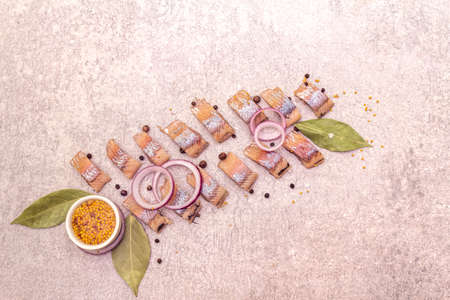 Pieces of pickled Norwegian salted herring with spices and onions. Marinated fish on a stone background, top view.