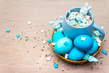 Easter kids hot sweet chocolate or cocoa with funny marshmallow bunny rabbits and easter eggs. On sand stone background, close up. Stock Photo - 137217226