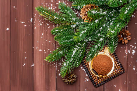 Festive dessert in the shape of a Christmas fir cone. New Year sweet treat concept. Wooden boards background, copy space, top view