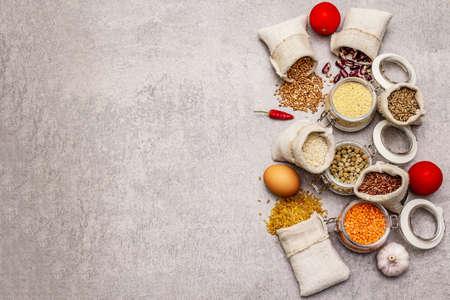 Concept d'achat de nourriture zéro déchet. Céréales, pâtes, légumineuses, champignons séchés, épices, légumes frais. Mode de vie durable, arrière-plan en béton de pierre, espace de copie, vue de dessus