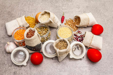 Zero waste food shopping concept. Cereals, pasta, legumes, dried mushrooms, spices, fresh vegetables. Sustainable lifestyle, stone concrete background, Close up