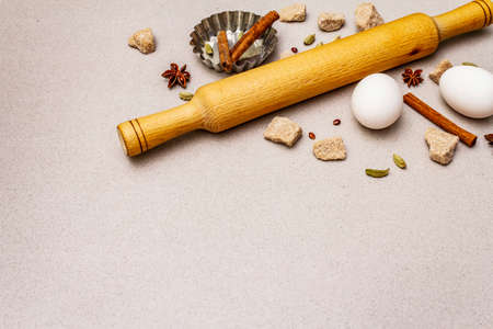 Christmas cooking background, spices, eggs, brown lump sugar, cupcake baking dish and a rolling pin. Light stone concrete background, copy space
